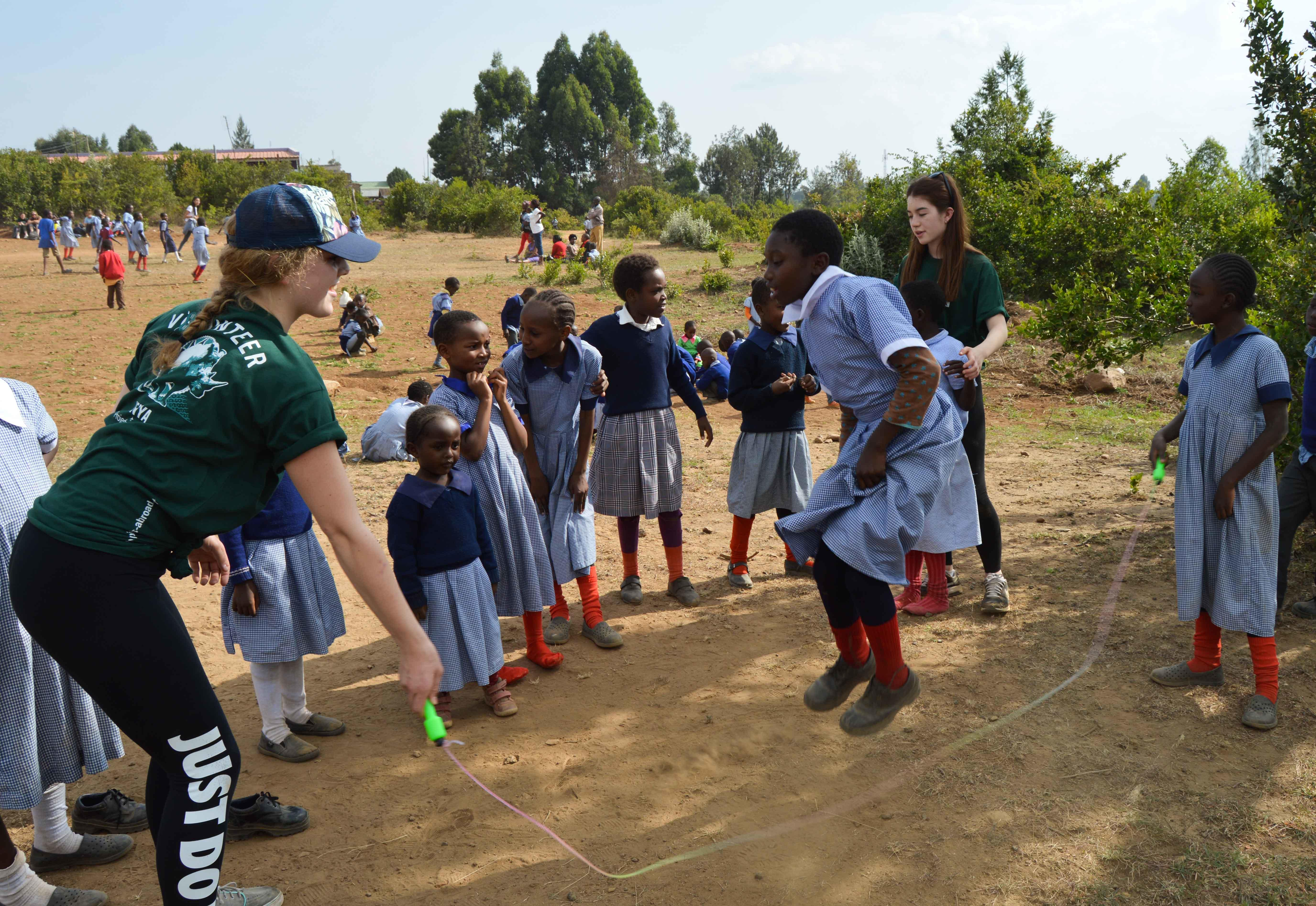 A Projects Abroad volunteer gets hands-on sports coaching experience in Kenya while running a fun activity with children